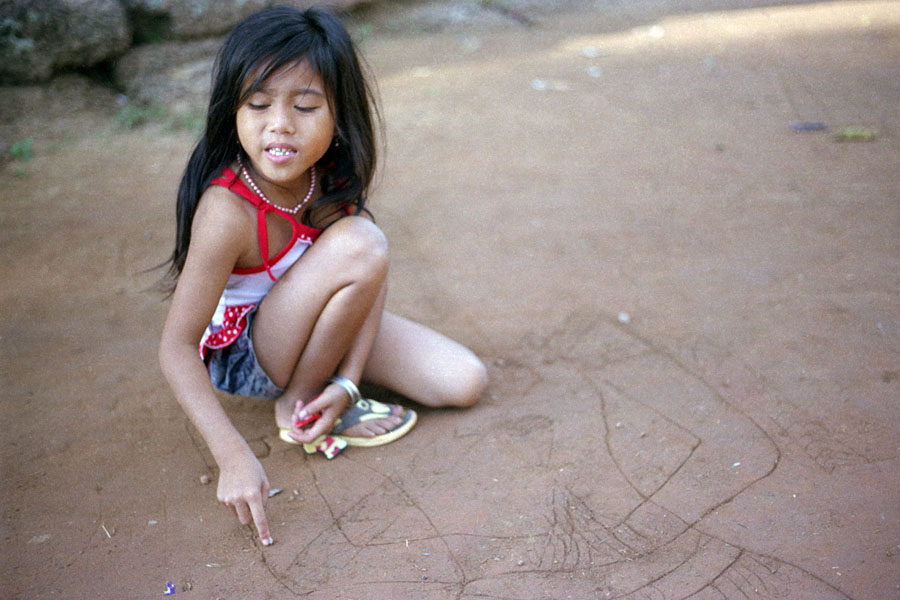 Angkor, Cambodia 2012: young girl drawing in the sand, asking for candy at Banteay Srei temple. Yes, she knew how to ask in Chinese. No, I don't know if she was drawing because she was bored while begging, or thought that people would be inclined to give her candy because she was drawing. Would have been a nice time to have a guide.
